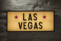 Close-up of Las Vegas signboard against gray wall