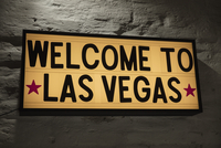 Close-up of Welcome To Las Vegas signboard against gray wall
