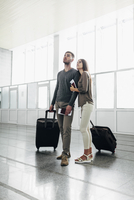 Full length of young couple with luggage and boarding passes at airport 11016034800| 写真素材・ストックフォト・画像・イラスト素材|アマナイメージズ