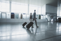Young couple with luggage walking at airport 11016034802| 写真素材・ストックフォト・画像・イラスト素材|アマナイメージズ