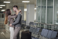 Side view of happy young couple embracing at airport