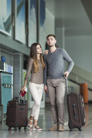 Full length of young couple with luggage waiting at airport 11016034822| 写真素材・ストックフォト・画像・イラスト素材|アマナイメージズ