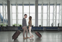 Full length side view of young couple with luggage looking at each other at airport 11016034826| 写真素材・ストックフォト・画像・イラスト素材|アマナイメージズ