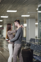 Side view of romantic young couple embracing at airport 11016034829| 写真素材・ストックフォト・画像・イラスト素材|アマナイメージズ
