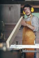 Carpenter examining plank of wood at workshop