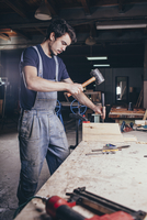 Carpenter using hammer and chisel on timber at workshop