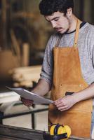Carpenter reading document at workshop