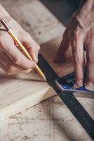 Cropped hands of carpenter marking on plank with pencil and ruler at workshop