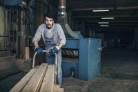 Carpenter pushing stack of wood planks on cart at workshop