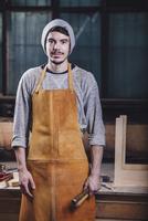 Portrait of carpenter holding hand tools at workshop