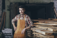 Portrait of carpenter standing by timber stack in workshop