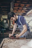 Carpenter planing timber at workshop