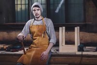Portrait of carpenter holding hammer while sitting on bench at workshop