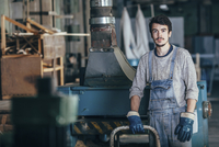 Portrait of carpenter standing by machinery at workshop