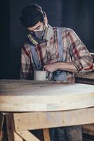 Man using electric sander on wood at workshop