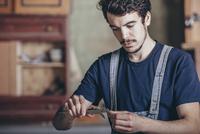 Carpenter using caliper in workshop