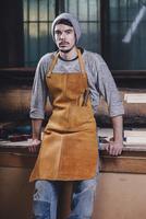 Portrait of carpenter sitting on bench at workshop