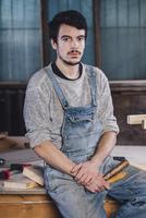 Portrait of young worker sitting with hand tools on bench