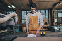 Carpenter reading document on bench in workshop