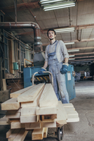 Worker standing with stack of planks on cart in carpentry workshop