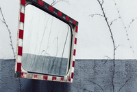 Low angle view of road mirror with reflection against wall