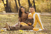 Portrait of parents sitting with cute baby boy in park during autumn
