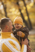 Cheerful baby boy being carried by father at park during autumn 11016034917| 写真素材・ストックフォト・画像・イラスト素材|アマナイメージズ
