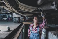 Female mechanic working underneath car at garage