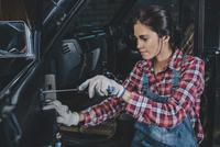 Female mechanic repairing car at workshop