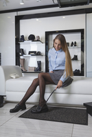 Young woman trying on shoes at store 11016034951| 写真素材・ストックフォト・画像・イラスト素材|アマナイメージズ