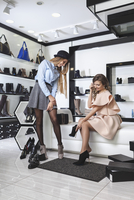 Happy female friends trying on shoes at store 11016034958| 写真素材・ストックフォト・画像・イラスト素材|アマナイメージズ