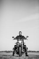 Full length portrait of biker sitting on motorcycle against clear sky