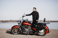 Full length portrait of biker standing by motorcycle and looking away at lakeshore