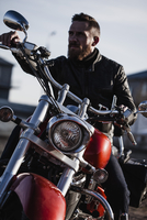 Portrait of biker sitting on motorcycle and looking away