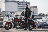 Full length portrait of biker holding helmet while standing by motorcycle against industrial setting 11016034968| 写真素材・ストックフォト・画像・イラスト素材|アマナイメージズ