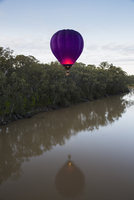 Hot air balloon over calm lake by trees