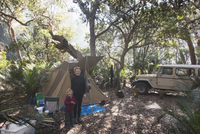 Portrait of mother and son standing outside tent in forest 11016034983| 写真素材・ストックフォト・画像・イラスト素材|アマナイメージズ