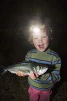 Portrait of cheerful boy wearing headlamp fish in forest