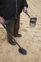 Low section of man holding metal detector while standing on sand