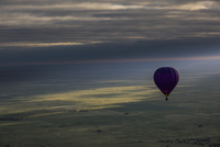 Hot air balloon over landscape against cloudy sky during sunset