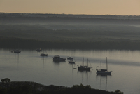 High angle view of sailboats on river in foggy weather during sunset