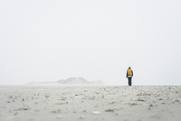 Rear view of female hiker walking on field against sky in foggy weather 11016035035| 写真素材・ストックフォト・画像・イラスト素材|アマナイメージズ