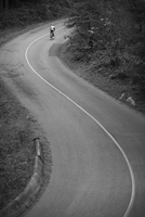 Distant view of cyclist riding bicycle on country road