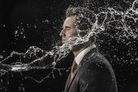 Water splashing on businessman against black background 11016035129| 写真素材・ストックフォト・画像・イラスト素材|アマナイメージズ