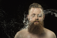Water splashing on man's face against black background