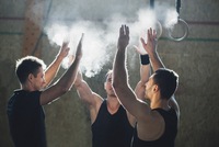 Determined male athletes dusting sports chalk together at gym
