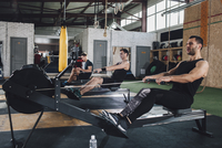 Determined men exercising on rowing machines at health club