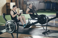 Determined men exercising on rowing machines at gym 11016035139| 写真素材・ストックフォト・画像・イラスト素材|アマナイメージズ