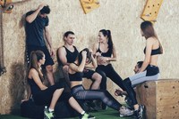 Happy male and female athletes relaxing after workout at gym