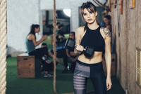 Portrait of confident female athlete lifting dumbbell at gym